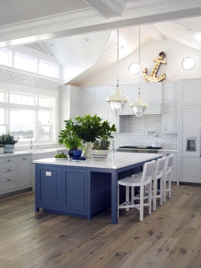 A remodeled kitchen in Coronado, California, that is functional and chic with a large parsons-style island, pale grey blue shaker cabinetry, and large industrial pendant lights, designed by Betsy Burnham of Burnham Design. (AP-Yonhap)