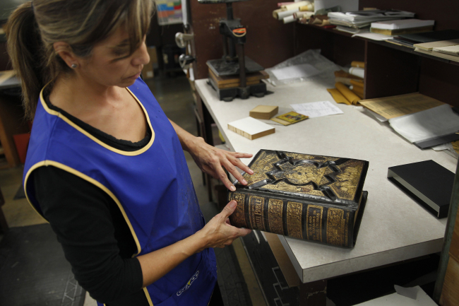 Restoration specialist Grace Sanchez restores leather on the cover of a family Bible from 1893 for a client at Kater-Crafts. (Allen J. Schaben/Los Angeles Times/TNS)