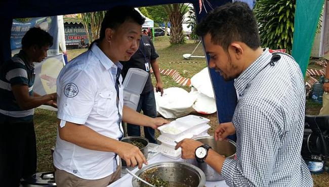 Businessman Ferry Alfiand serves food, which he brought from his restaurant, to the search personnel at the operations center. (Straits Times)
