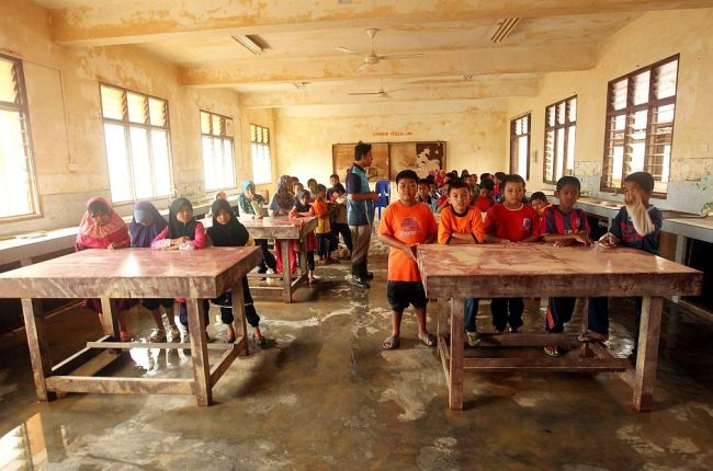 Pupils of SK Manek Urai starting their first day in school with whatever furniture was left by the floods. (The Star)