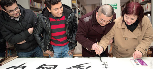 A calligraphy expert shows students how to use a traditional brush pen in Hefei, Anhui province, China, on Jan. 13. (China Daily)