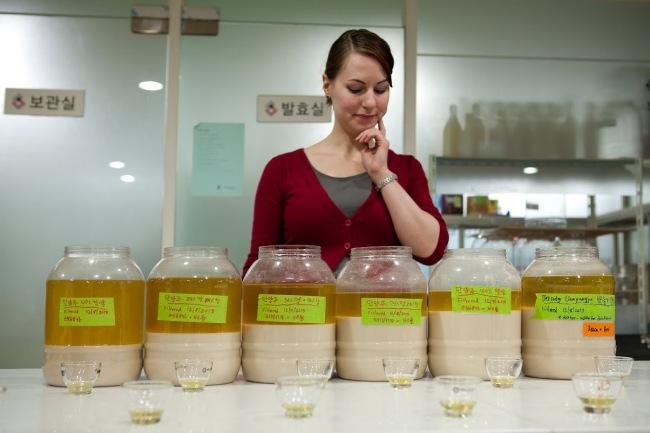 Instructor Becca Baldwin checks a selection of makgeolli brews at Susubori Academy in Seoul. (Eun Kyung Jun)
