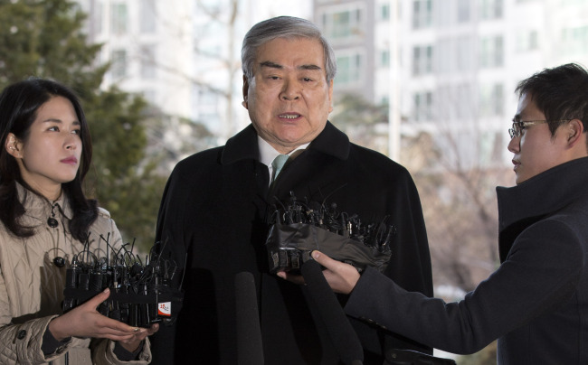 Korean Air chairman Cho Yang-ho answers questions from reporters before stepping into a court in Seoul on Friday. (Yonhap)