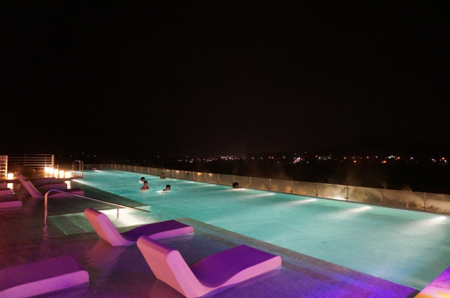 Hotel guests enjoy a night view of Seogwipo, Jejudo Island, from the rooftop infinity swimming pool at Kensington Jeju Hotel. (Lee Woo-young/The Korea Herald)