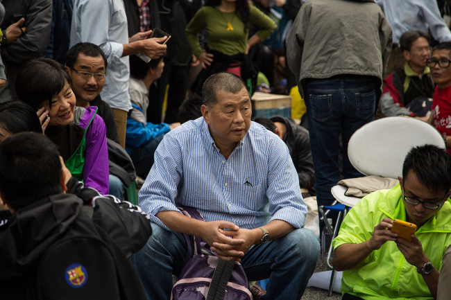Jimmy Lai, chairman of Next Media Ltd. (center) sits among protesters outside the Central Government Offices in the Admiralty district of Hong Kong on Dec. 11. (Bloomberg)