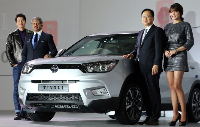 Mahindra Group chairman Anand Mahindra (second from left) poses next to the newly launched compact SUV, jointly developed by the group's Korean arm Ssangyong Motor, with other company officials at a launch in Seoul on Jan. 13. (Yonhap)