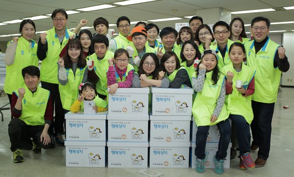 """Hana Financial Group officials pose after helping to prepare a """"Happy Box"""" to be sent to disadvantaged Seoul citizens early this month. (Hana Financial)"""