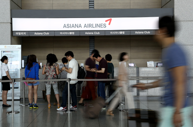 Travelers walk past the Asiana Airlines Inc. Asiana Club counter as other travelers stand in line at Incheon International Airport in Incheon. (Bloomberg)