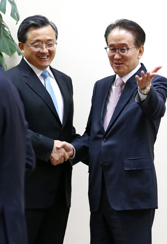 Deputy foreign ministers of China and South Korea join hands at a trilateral meeting in Seoul, September 2014. Liu Zhenmin (left) from China and Lee Kyung-soo from Korea. (Yonhap)