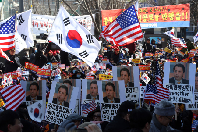 Activists wave national flags of Korea and the U.S. along with pickets condemning pro-North Korean forces on March 10 in Gwanghwamun, Seoul, following a knife attack by a radical activist on U.S. Ambassador to Korea Mark Lippert on March 5. (Yonhap)