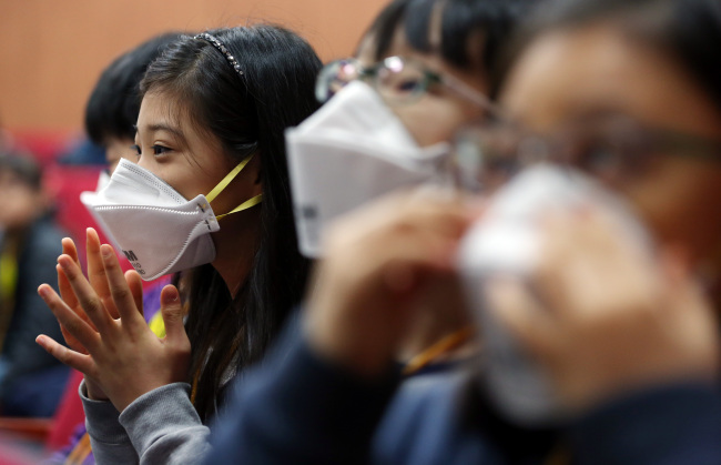 Students learn how to wear protective masks at Gangseo Elementary School in western Seoul last week. (Yonhap)