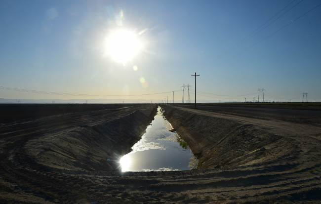 Water flows along a canal near fields of crops beneath the sweltering sun in Kern County, California. (AFP-Yonhap)