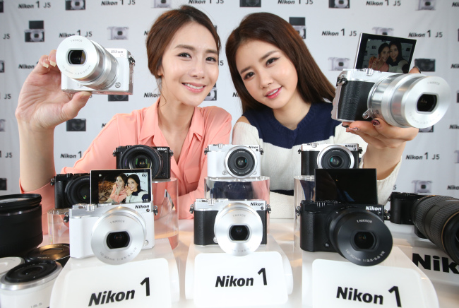 Models pose with Japanese camera-maker Nikon's new interchangeable-lens digital camera, Nikon 1 J5, at an unveiling event of the product in Seoul on Thursday. The digital camera is capable of shooting 20 continuous frames per second and features a 20.8 megapixel image sensor that allows 4K video recording. (Yonhap)