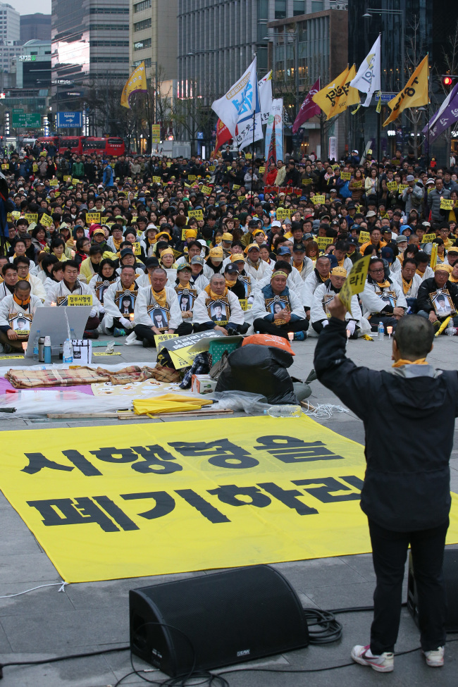 Families of those killed in the Sewol ferry disaster hold a rally in Seoul, Sunday. They demanded the government rewrite the mandate on investigating the cause and measures related to the disaster. (Yonhap)