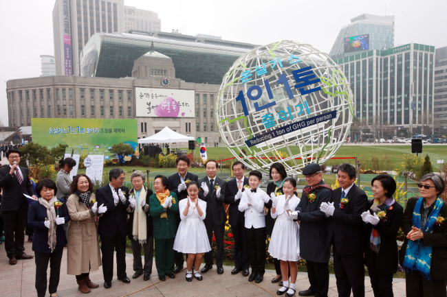 """Seoul Mayor Park Won-soon (center) and other participants clap after unveiling the sculpture for the civic campaign """"Reducing 1 Ton of Greenhouse Gas Per Person"""" at Seoul Plaza on Friday. (Yonhap)"""