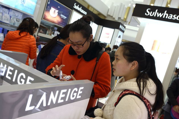 A Chinese tourist (center) samples AmorePacific's Laneige cosmetics at a Lotte Duty Free store on Jejudo Island. (Bloomberg)