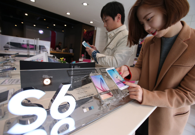 A customer checks out a Samsung Galaxy S6 Edge phone at a LG Uplus retail outlet in Jongno, central Seoul, on Friday. Samsung Electronics' new flagship smartphones, the Galaxy S6 and S6 Edge, go on sale Friday worldwide. (Yonhap)