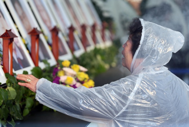 A victim's family member cries while laying a flower at a memorial held in Incheon to mark the first anniversary of the Sewol ferry disaster on Thursday. (Yonhap)
