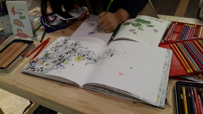 A bookstore offers a table with color pencils and coloring books for visitors to try out (Ahn Sung-mi/The Korea Herald)