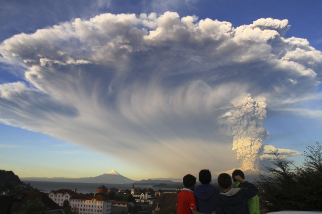 Children in Puerto Varas, Chile, watch the Calbuco volcano erupt on Wednesday. The eruption sent a huge ash cloud over a sparsely populated, mountainous area in southern Chile. (Related story on Page 6) (AP-Yonhap)