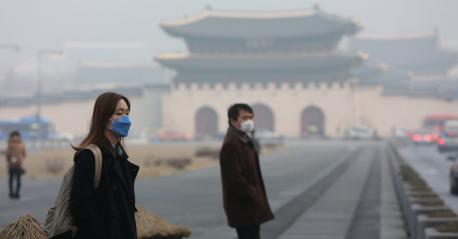 Citizens wear masks while walking around Gwanghwamun Plaza in Seoul in February, during which the country reported high levels of ultrafine dust. (Yonhap)