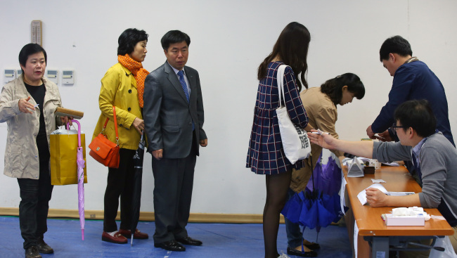 Voters line up to cast their ballots in Seoul on Wednesday. Yonhap