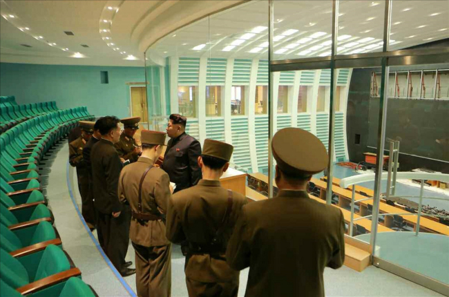 North Korean leader Kim Jong-un (third from right) speaks with officials during his visit to a newly built satellite control and command center. (Yonhap)