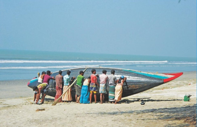 A group of people prepare a boat to sail from Khurer Mukh in Teknaf. This is one of the starting points of trafficking to Malaysia. (The Daily Star)