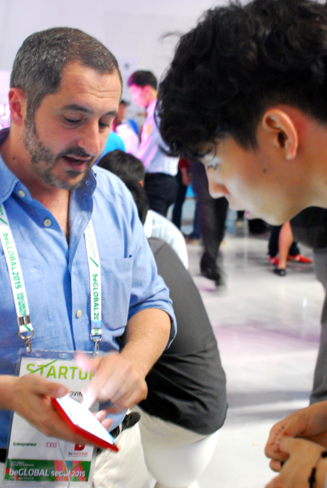 Raffaele Giovine (left), CEO of Italist, demonstrates his service to an attendee of beGLOBAL, a global tech conference in Seoul on May 14. (Elaine Ramirez/The Korea Herald)
