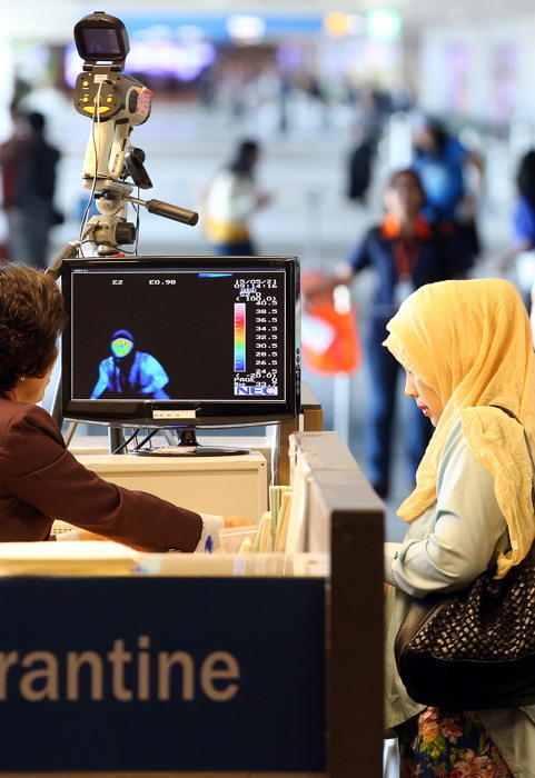 Passengers arriving from the Middle East pass by a thermal camera at Incheon airport on May 21. (Yonhap)