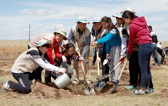 Employees of Korean Air and Mongolian residents plant trees in the Baganuur Desert in Mongolia on Tuesday. (Korean Air)