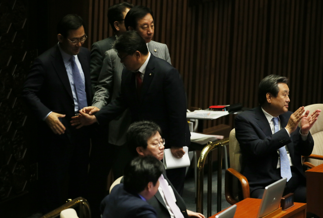 Saenuri Party leader Rep. Kim Moo-sung (right) claps as the plenary session wrapped up after some 60 bills, including the contentious civil pension reform, were endorsed early Friday at the National Assembly. (Yonhap)