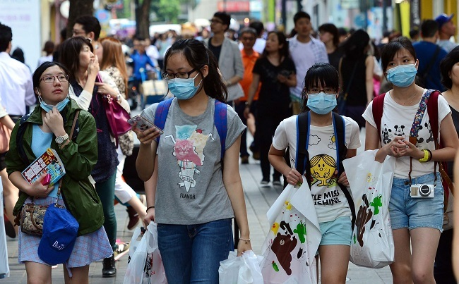 Tourists wearing masks walk along a street in Myeong-dong, downtown Seoul, Wednesday (Yoon Byung-chan / The Korea Herald)