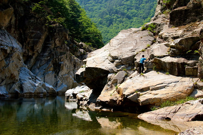 A hiker climbs up the rocky trails of the Wangpicheon Valley in Uljin, North Gyeongsang Province. (Julie Jackson/The Korea Herald)