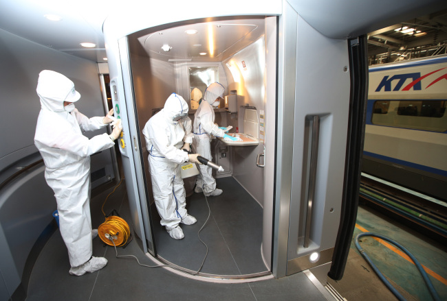 KTX officials sterilize the inside of a train in Goyang, Gyeonggi Province, in an effort to prevent the spread of MERS on Friday. (Yonhap)