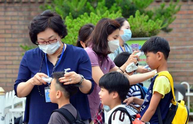Students get their temperatures checked before entering Hongpa Elementary School in Seoul on Monday. (Yoon Byung-chan/The Korea Herald)