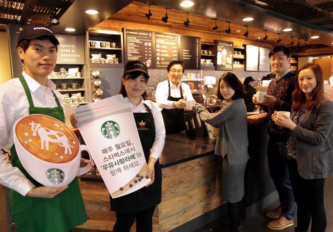 Starbucks Coffee Korea CEO Lee Seock-koo (third from left) attends a campaign to promote milk consumption at the coffeehouse's Sogong-dong shop in central Seoul. (Starbucks Coffee Korea)