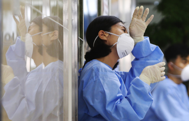 A medical staff member wipes the sweat off her brow during a break after treating patients placed in quarantine at Daecheong Hospital in Daejeon on Friday. (Yonhap)