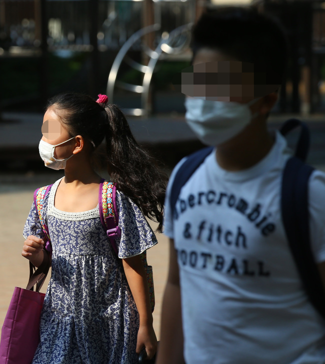 Students wearing masks enter an elementary school in Seoul, which resumed classes after a weeklong shutdown last week. (Yonhap)