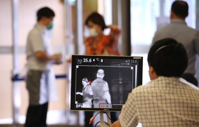 Employees of Konkuk University Medical Center in Seoul check visitors for potential fever on Monday after the hospital confirmed its first MERS patient. (Yonhap)