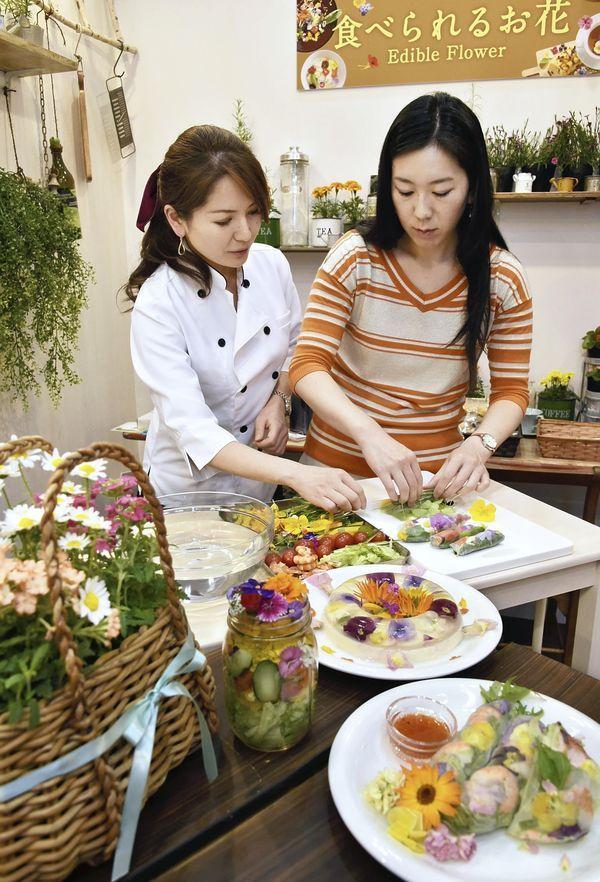 Yomiuri Shimbun writer Mayumi Oshige, right, makes Vietnamese spring rolls using edible flowers under the instruction of food researcher Can'Na in Koto Ward, Tokyo. Yomiuri Shimbun