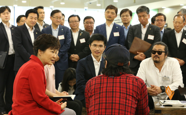 President Park Geun-hye talks with participants during the launch of the Jeju Center for Creative Economy and Innovation on Friday. Jeju Gov. Won Hee-ryong (left, standing), Daum Kakao chairman Kim Bum-soo (center, standing) and AmorePacific chairman Suh Kyung-bae (third from left, standing) attended the opening ceremony. (Yonhap)