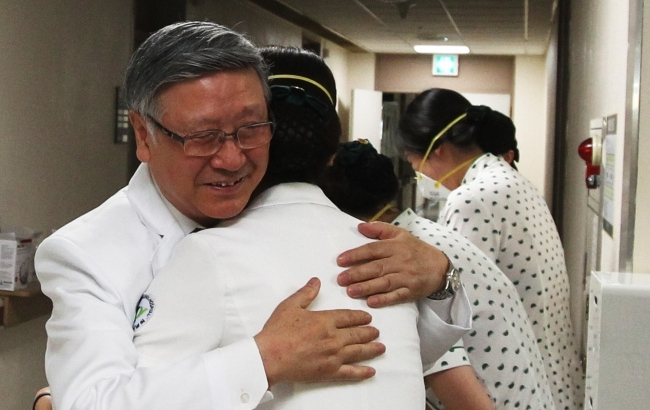 Park Chang-il, director of Konyang University Hospital in Daejeon, hugs the medical staff after the hospital reopened Friday. (Yonhap)