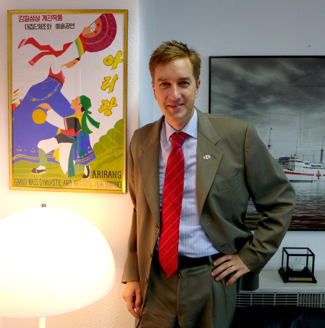 Danish Ambassador Thomas Lehmann poses beside an Arirang Mass Games poster he obtained on a visit to North Korea in late May. Joel Lee/The Korea Herald