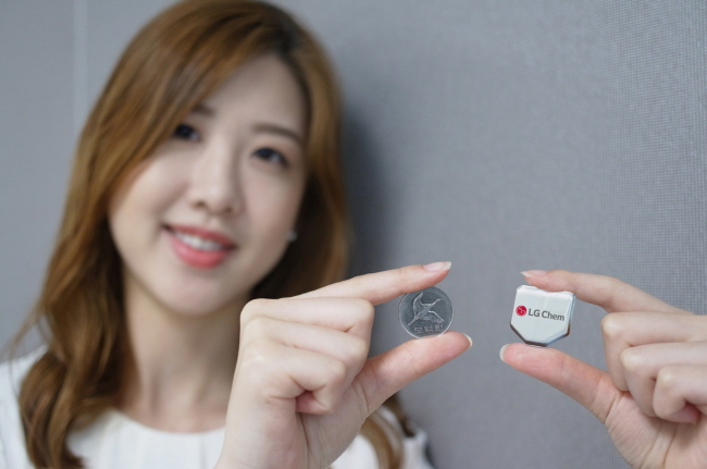 An LG Chem staffer poses with the firm's hexagonal battery. LG Chem