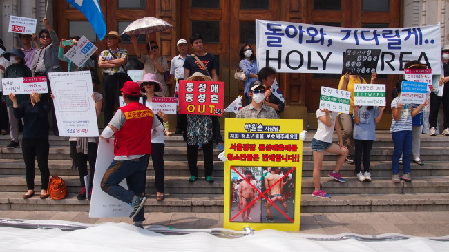 Antigay groups hold placards that read