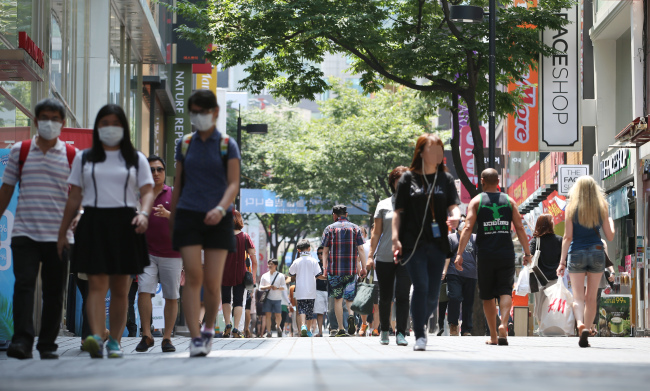 Some tourists wear masks to prevent themselves contracting MERS while walking at Myeongdong shopping district in central Seoul on Sunday. (Yonhap)