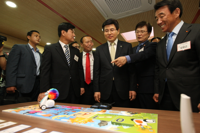 Prime Minister Hwang Kyo-ahn (third from right) and ICT Minister Choi Yang-hee (second from right) look at smart robots displayed at SK Group's Center for Creative Economy and Innovation, which opened on Tuesday in Sejong City. At right is SK Group's SUPEX Council chairman Kim Chang-keun. (ICT Ministry)