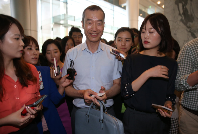 Samsung C&T CEO Choi Chi-hun surrounded by reporters (Yonhap)