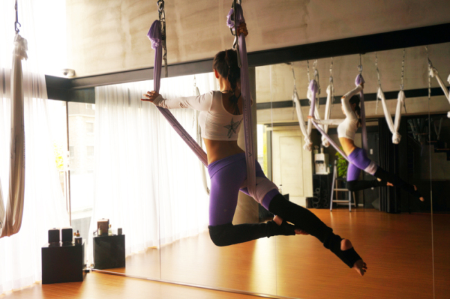 """Instructor Lucia Kim demonstrates the """"Luna"""" pose. (Flying Yoga in New York)"""